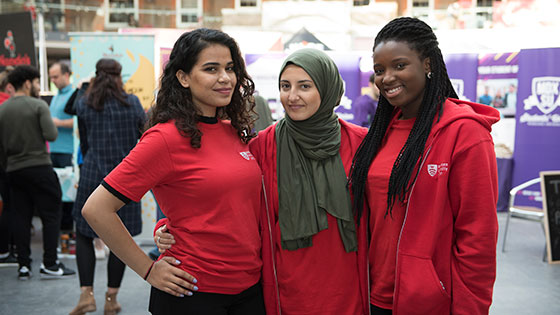 Three students in Middlesex red t-shirts working during an Open Day