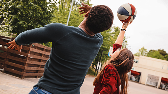 Two Middlesex University students playing basketball on campus