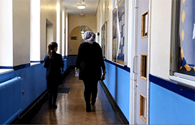 A Psychology placement student walks with a pupil at her placement school