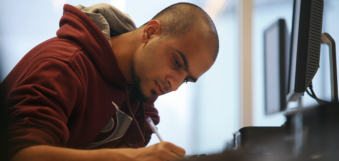 A student studying a MOOC studies in front of a computer