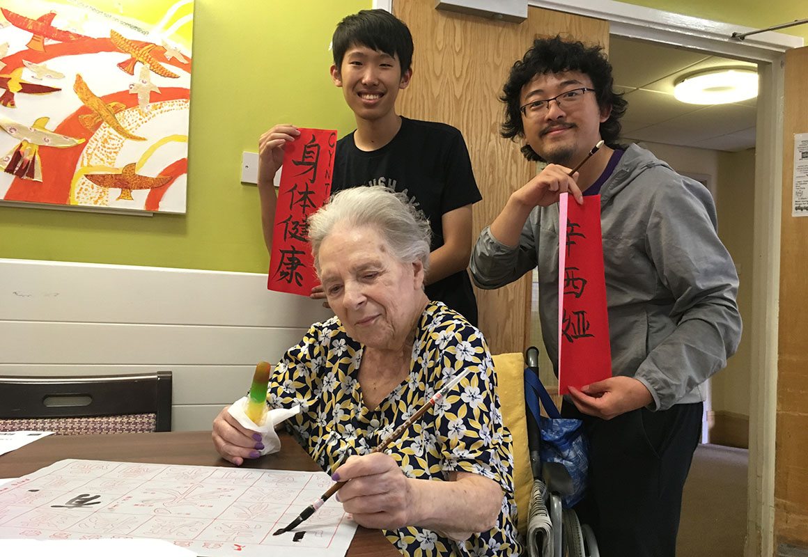 Chinese students teaching calligraphy to lady at Clore Manor care home