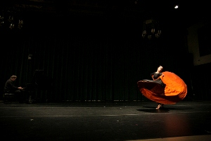 A dancer performs a solo as a pianist plays in the background
