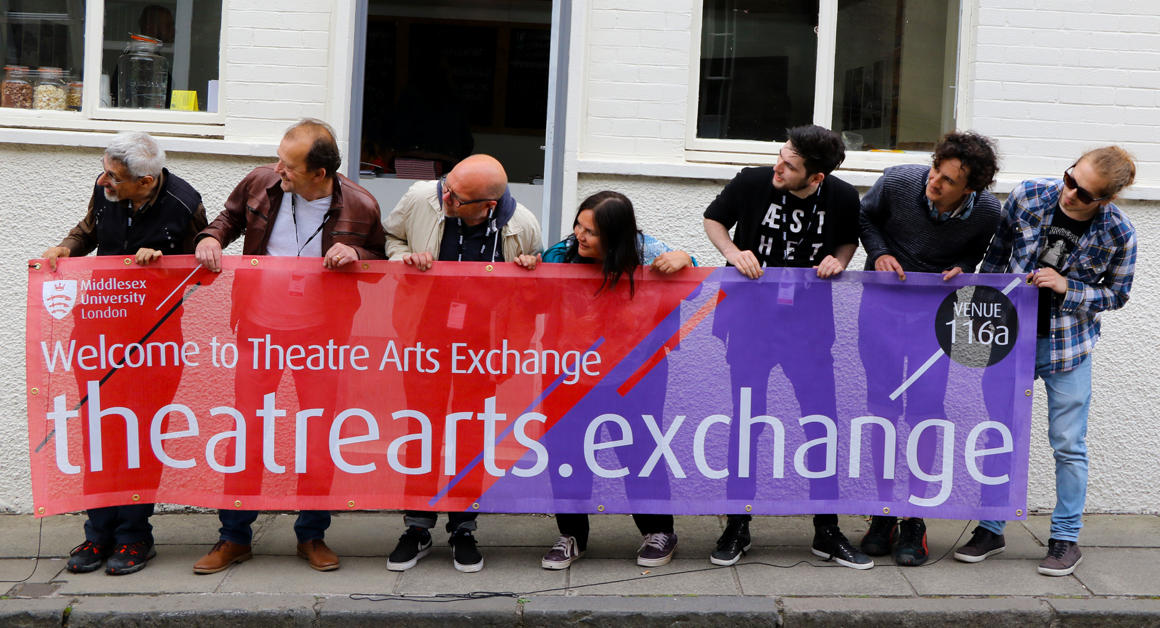 The Theatre Arts Exchange team hold the venue's banner outside the pop-up theatre