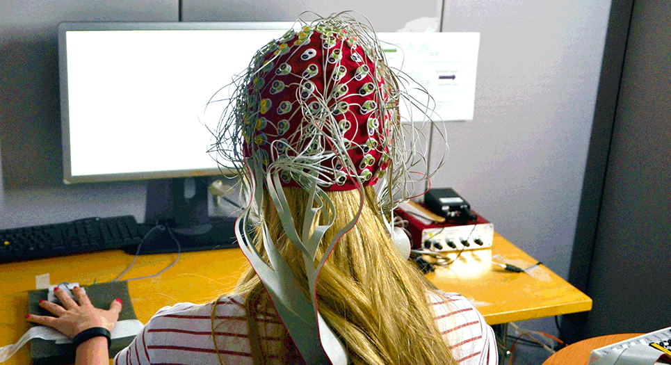 A Psychology researcher uses EEG equipment on a participant