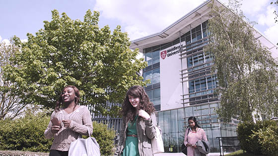 Undergraduate students walking outside Middlesex University