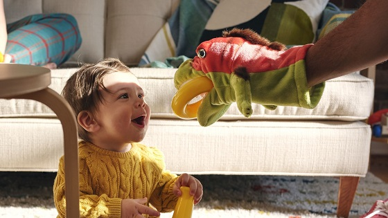 A parent playing with a hand puppet to entertain their toddler