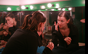 A Theatre Arts student applies make-up in the dressing room before a performance