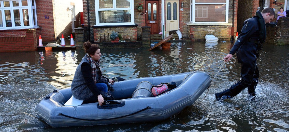 A soldier with 36 Royal Engineer Regiment helps a local resident in a boat in the flood hit Surrey town of Egham.