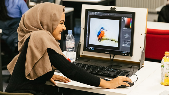 A student using a graphic design programme on a computer