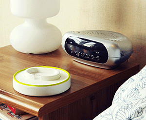 The Aware wristband sitting on its charging dock on a bedside table