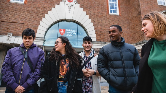 Students laughing in front of the Middlesex University main building