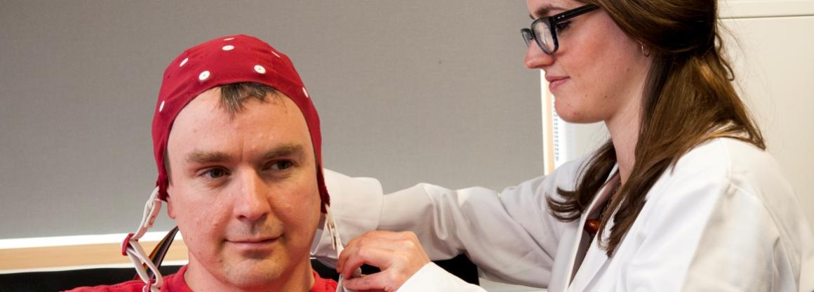 A psychology researcher places an EEG cap on a man's head