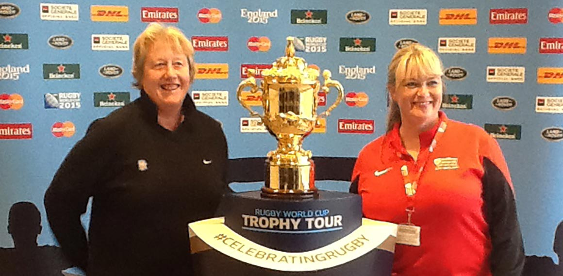 Associate Professors Ange Cumine and Clare Deary pose with the Rugby World Cup's Web Ellis Cup